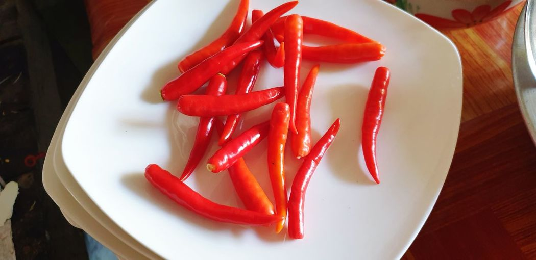 High angle view of red chili peppers in plate on table