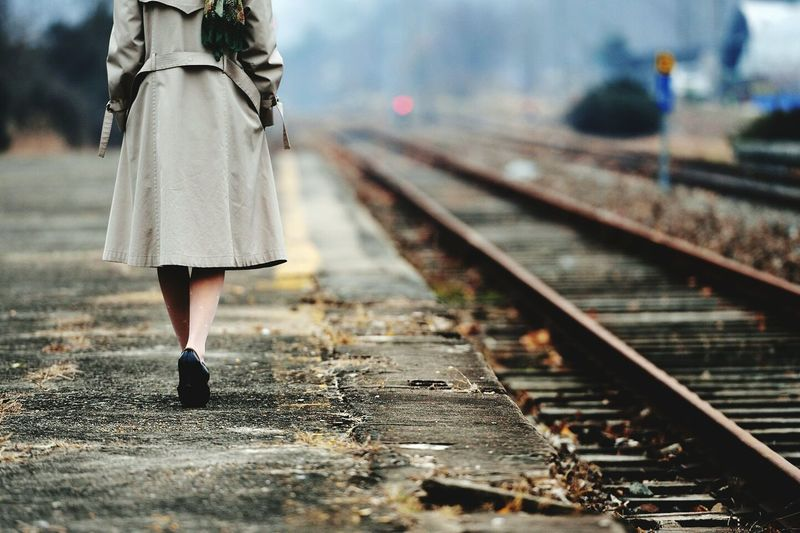 Low section of woman walking at railroad station platform