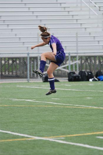 Female soccer player heading ball