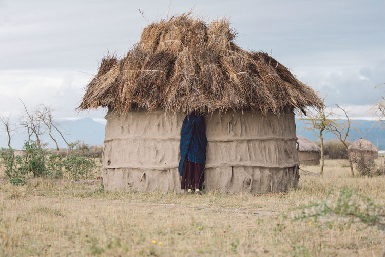 View of masai woman under cottage roof