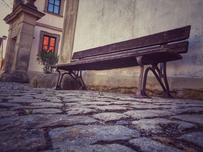 Empty bench on table by building