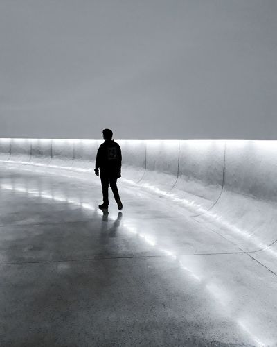Rear view of silhouette man walking on illuminated road