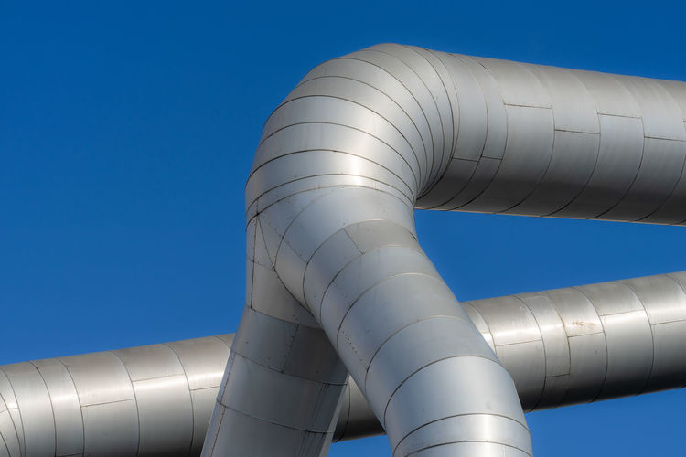 Low angle view of pipe against clear blue sky