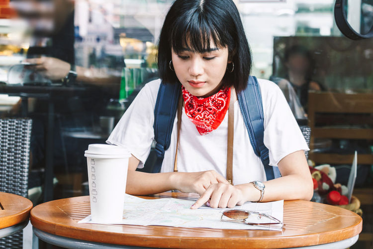 Young woman reading map while sitting at sidewalk cafe