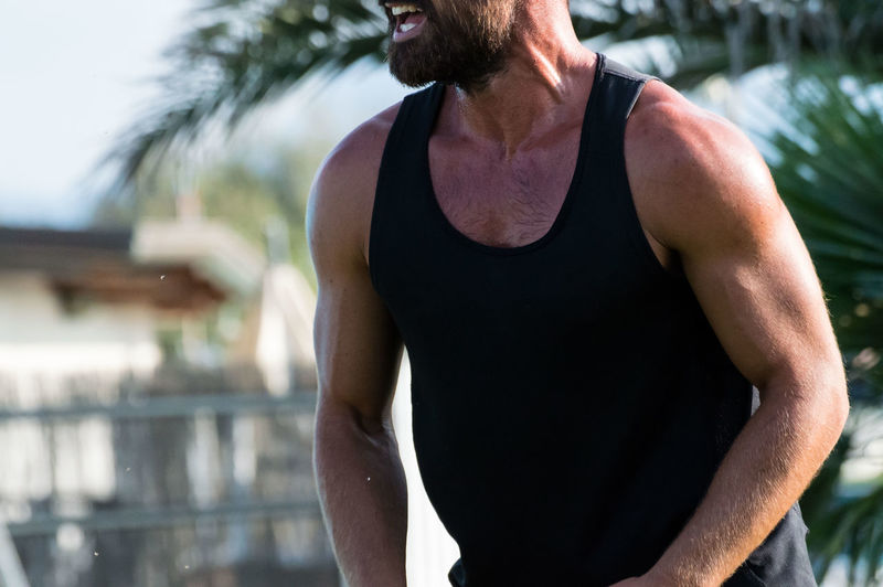Midsection of muscular man standing outdoors