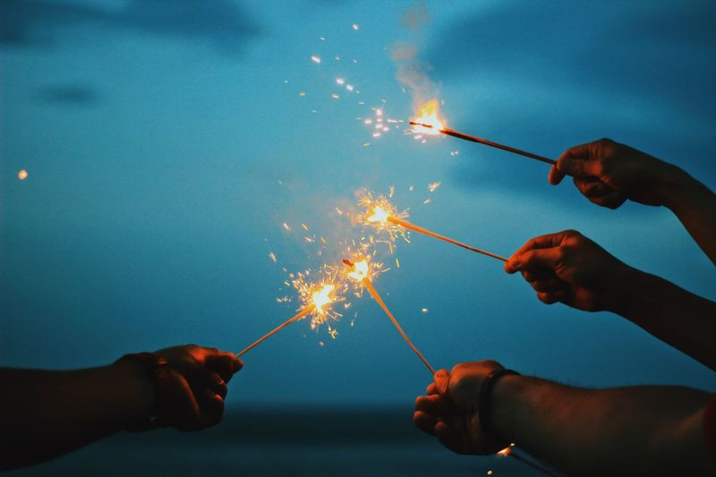Cropped hands holding lit sparkler against sky