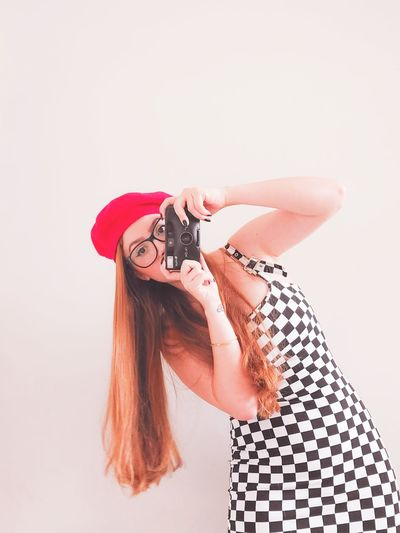 Portrait of young woman photographing with camera against white background