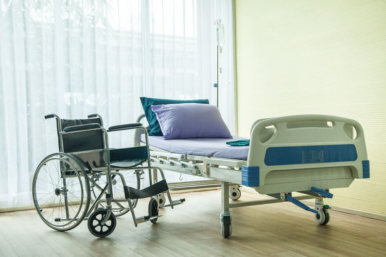 wheelchair and bed in the hospital waiting used for sick people. the bed near window have light from sun shine Absence Architecture Bed Building Computer Curtain Day Empty Furniture Healthcare And Medicine Hospital Hospital Ward Indoors  Medical Equipment No People Recovery Sick Technology Wheel Wheelchair Window