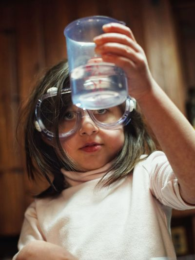 Girl Wearing Protective Eyewear Looking At Liquid In Container At Home