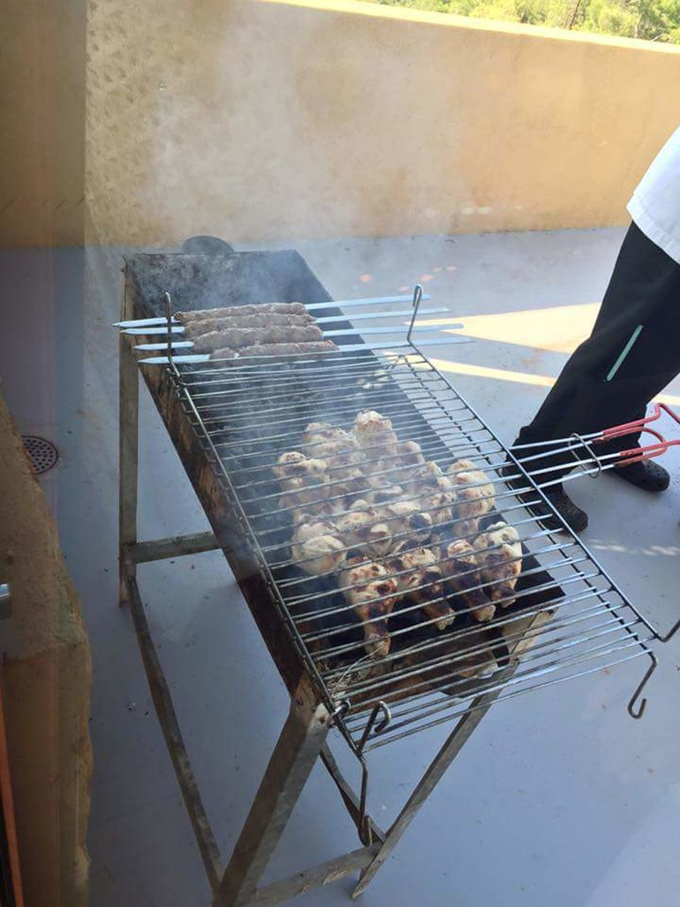 barbecue grill, barbecue, grilled, preparation, food and drink, food, heat - temperature, smoke - physical structure, meat, preparing food, roasted, day, one person, real people, outdoors, freshness, metal grate, serving tongs, people