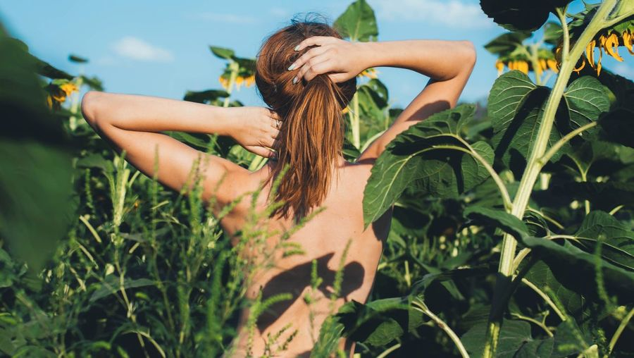 Rear View Of Topless Standing Amidst Plants