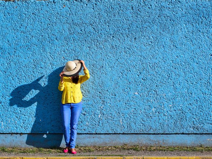 Full length of girl standing against blue wall