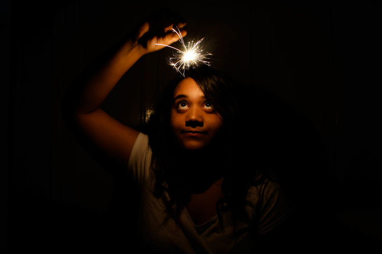Girl holding lit sparkler in night