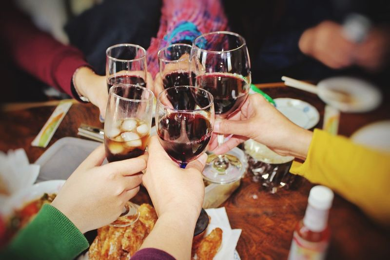 Cropped Hands Toasting Red Wineglasses Over Table