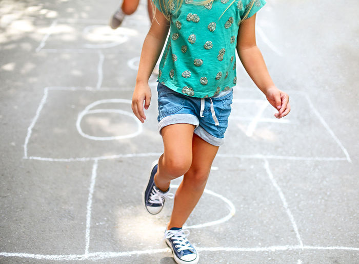 Low section of girl playing hopscotch