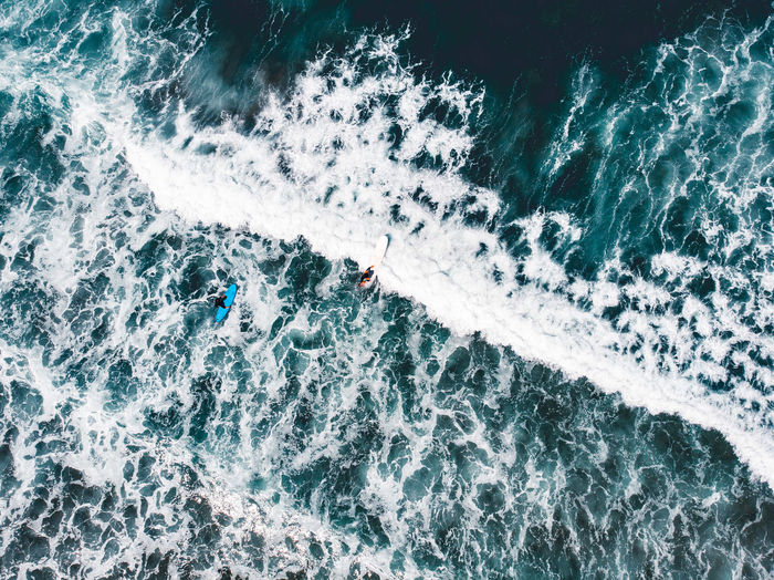 Aerial drone view over surfers with blue water and white waves in portugal.
