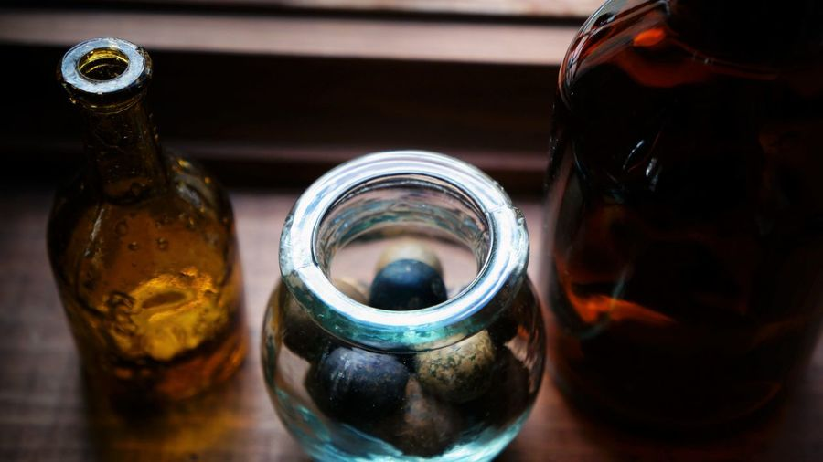 Close-up of glass containers on windowsill