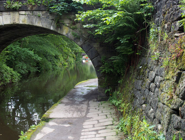Path along the rochdale canal  under an old stone bridge with vegetation and  trees and a narrowboat