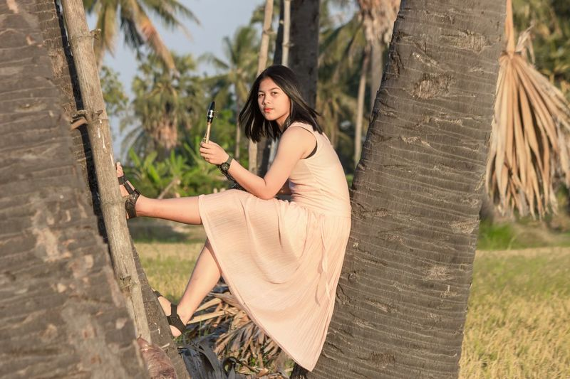 Young woman sitting on tree trunk with saxophone