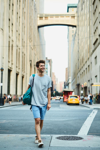 Portrait of young man standing on road in city