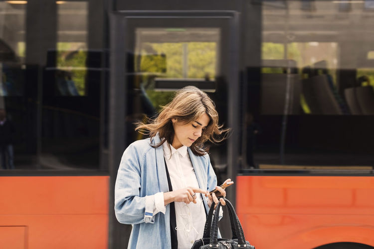 Woman looking at camera while standing on bus