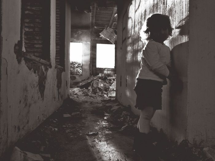 Rear view of woman standing in abandoned building
