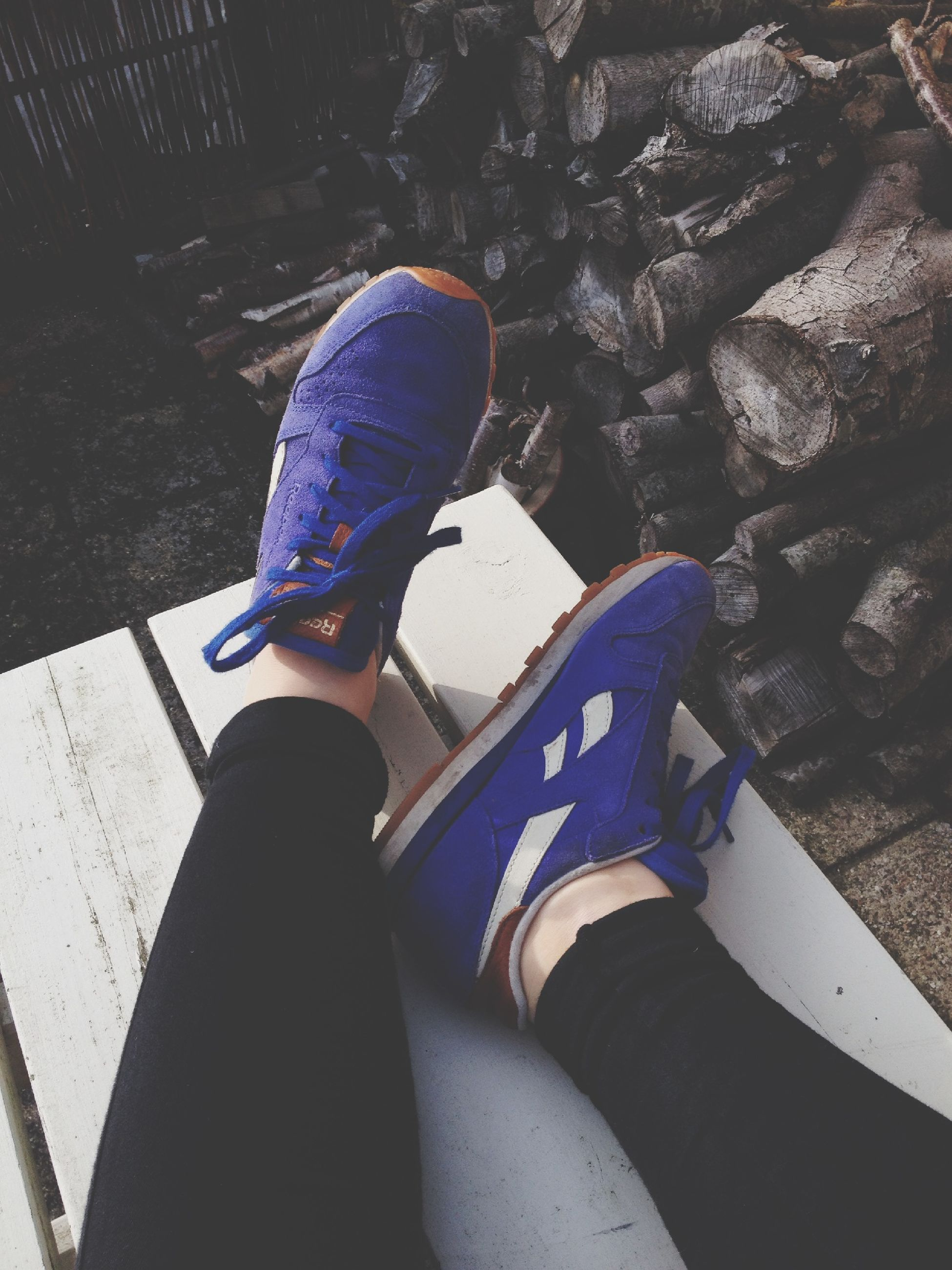 low section, person, lifestyles, shoe, personal perspective, high angle view, leisure activity, standing, footwear, men, human foot, jeans, casual clothing, outdoors, blue, sunlight