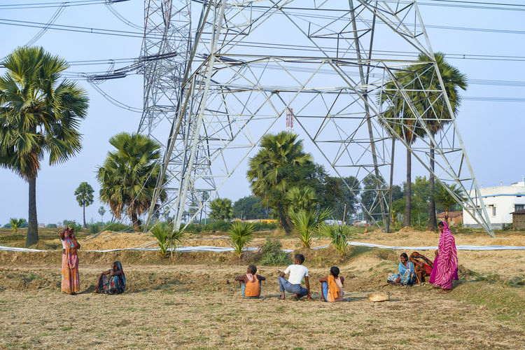 Group of rural people sitting in front of a huge high voltage power pylon Rural Landscape Fuel And Power Generation People Group Day Field Sky Rural Scene India Bihar Power Supply Outdoors Sitting Electricity Pylon Electricity  Technology Land Women Nature Real People Group Of People Editorial Use Only