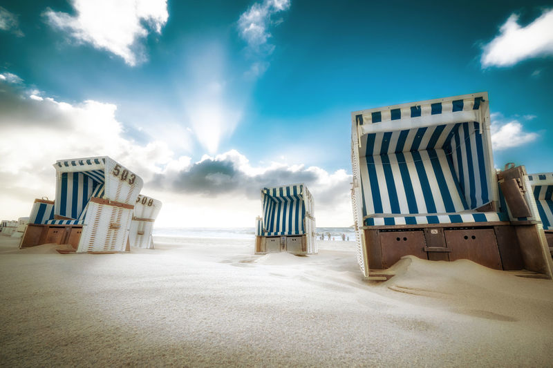 Hooded Chairs At Beach Against Blue Sky