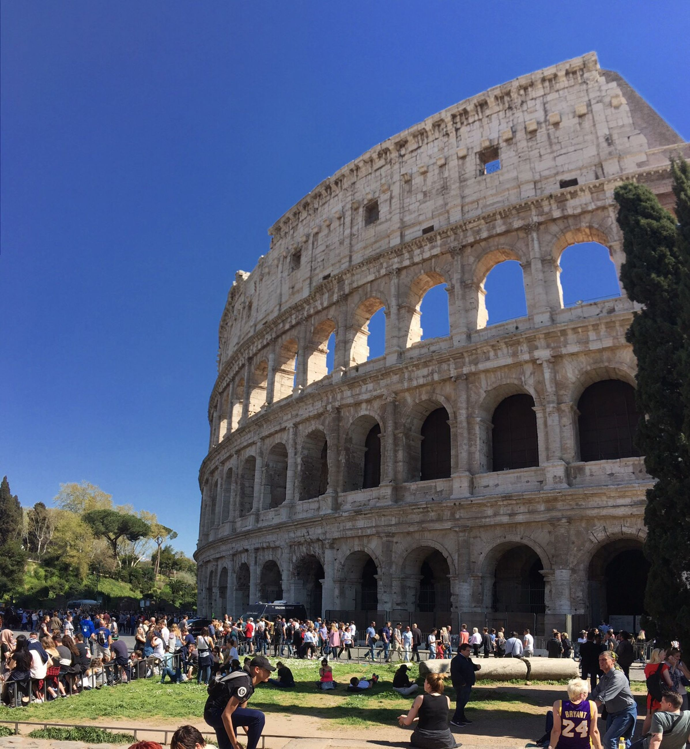 tourism, architecture, history, real people, travel destinations, tourist, blue, travel, built structure, old ruin, ancient, amphitheater, lifestyles, the past, building exterior, large group of people, low angle view, cultures, outdoors, city, sky, women, leisure activity, men, ancient civilization, day, crowd, people