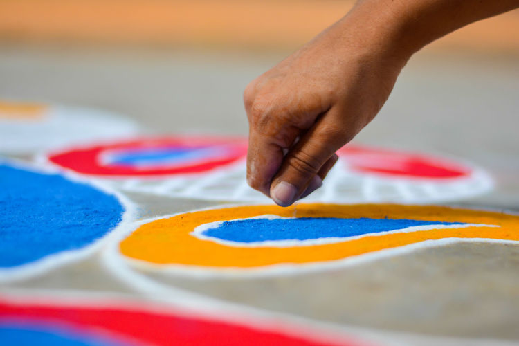 Close-Up Of Human Hand Making Rangoli On Footpath