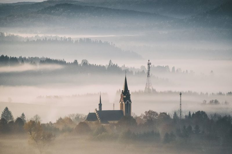 Cathedral Against Mountains During Foggy Weather