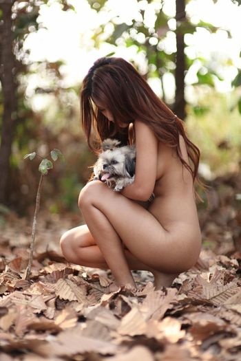 Naked woman with dog crouching on field