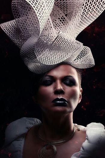 Woman wearing white headwear against black background