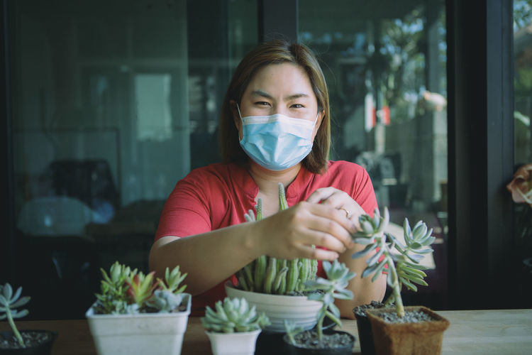 Portrait of woman wearing mask sitting by potted plant