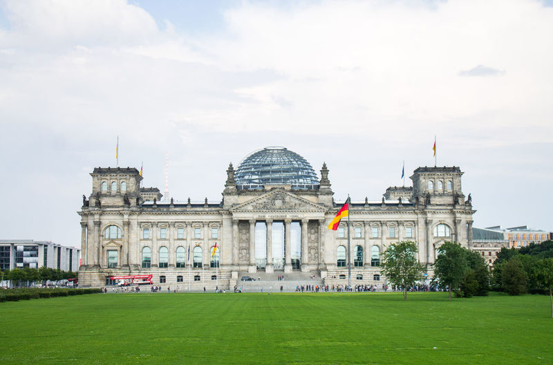 Facade of reichstag building against cloudy sky