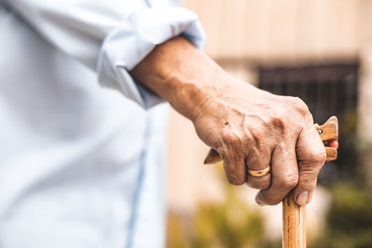 Midsection of person holding walking cane