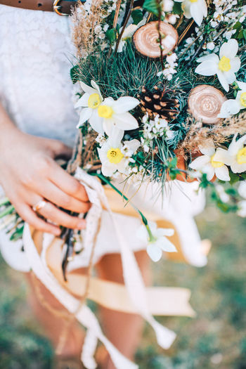 High angle view of bride holding bunch of flowers