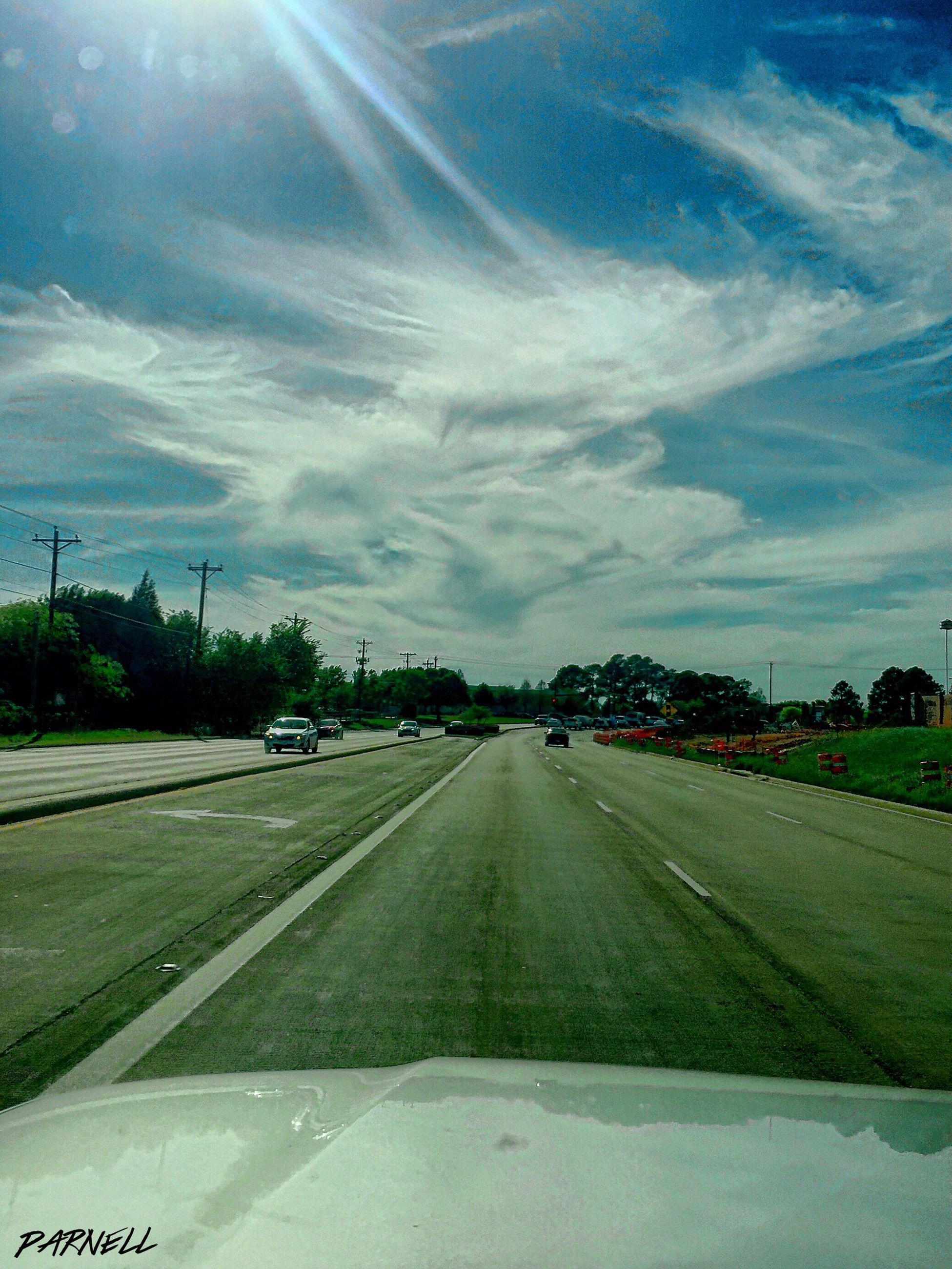 transportation, road, sky, the way forward, road marking, cloud - sky, car, diminishing perspective, vanishing point, mode of transport, windshield, land vehicle, country road, cloud, street, landscape, vehicle interior, nature, field, day