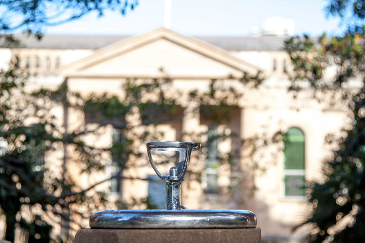 Water fountain sprout with a classic building in the background Cityscape Fountain Architecture Building Exterior Built Structure Close-up Day Focus On Foreground Nature No People Outdoors Sky Tree Water Fountain