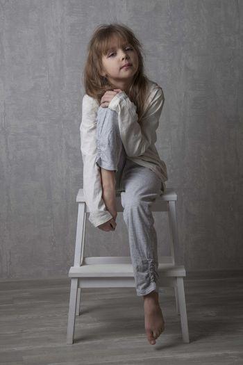 Portrait of girl sitting on step ladder