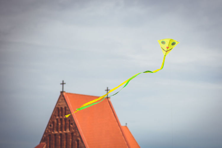 Low angle view of kite flying by church in city