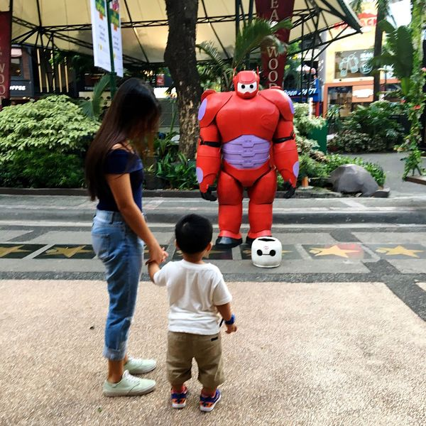 A boy watches a street artist dressed as an armoured Baymax at Eastwood, Quezon City in Metro Manila. Full Length Childhood Togetherness Boys Love Son Real People Black Hair Tree Casual Clothing Day Rear View Leisure Activity Two People Growth Standing Outdoors Men Child Street Artist Live Statue Baymax Manila Philippines
