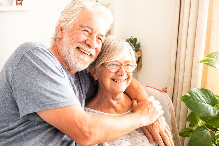 Senior couple smiling and enjoying the adult people with gray and white hair sitting in armchair. Natural plants in background. Bright window 70 Years Activity Adult Aged Armchair Background Beard Bright Casual Caucasian Connection Couple Decoration Domestic Elderly Emotion Enjoying Eyeglasses  Grandparents Gray Hair Hands Home Hug Inside Light Love Man Mobile Phone Natural News Old Pensioner Photo Plant Positivity Retired Retirement Senior Serene Sitting Smiling Sun Sunlight Tablet Technology Tenderness White Window Woman Senior Adult