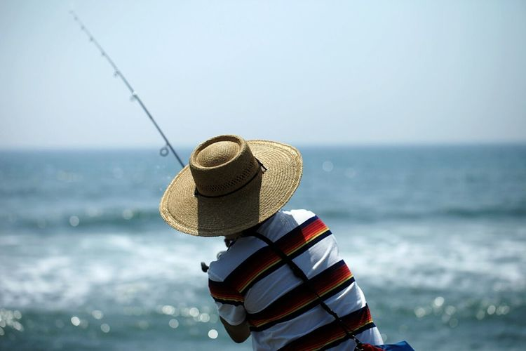 Rear view of man in hat fishing on beach