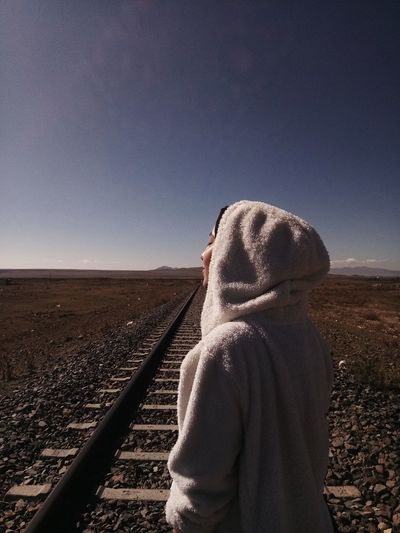 Woman wearing hooded shirt standing on railroad tracks against clear sky