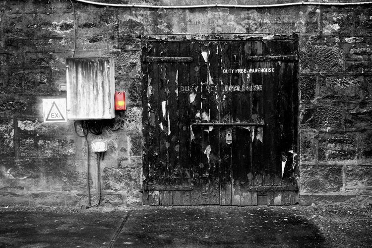 Warehouse door of a whiskey distillery Duty Free EyeEm Best Shots Industrial Red Scotland Architecture Black And White Blackandwhite Building Exterior Built Structure Coloursplash Distillery Door Electricity  Eye4photography  Indusrty Lock Locked Door No People Outdoors Warehouse Whiskey Wood - Material Wooden Door