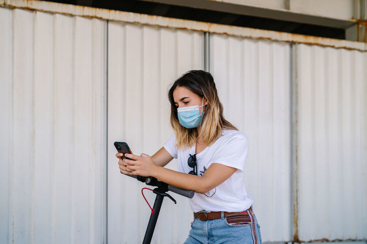 Young woman using mobile phone while standing on wall