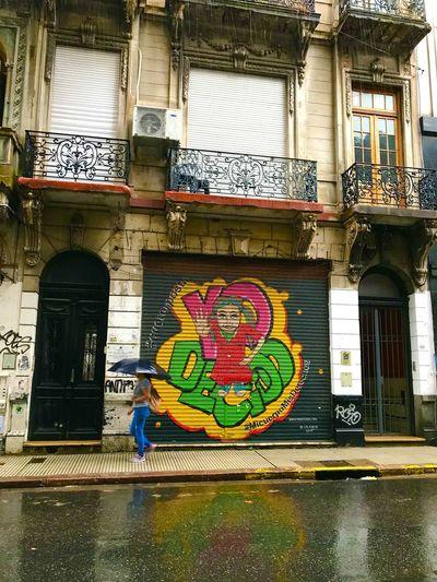 Graffiti on building seen through wet window