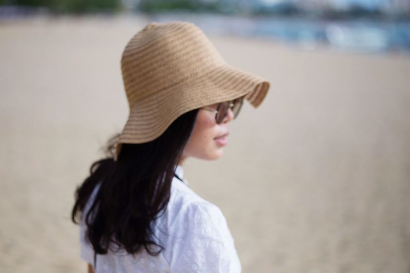 Side view of woman wearing hat standing at beach